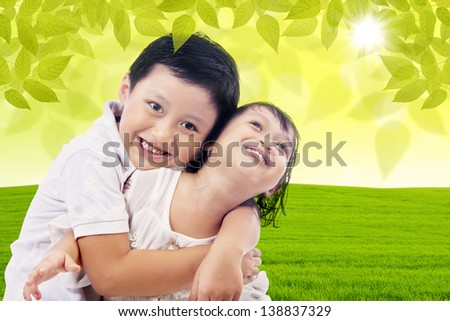 Loving brother hugging her sister at the park