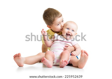 Loving brother kissing baby sister isolated on white background - stock photo