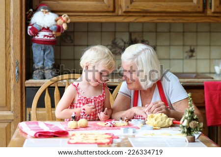 Loving caring grandmother, beautiful senior woman, baking tasty christmas cookies together with her granddaughter, cute little toddler girl, sitting at the table in classic traditional wooden kitchen - stock photo