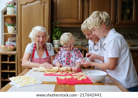 Loving caring grandmother, beautiful senior woman, baking tasty sweet cookies together with her grandchildren, cute little girl and two boys, sitting at the table in classic traditional wooden kitchen