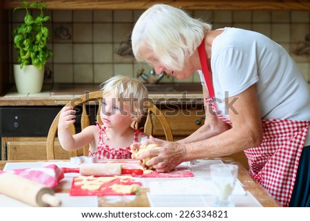 Loving caring grandmother, beautiful senior woman, baking tasty sweet cookies together with her granddaughter, cute little toddler girl, sitting at the table in classic traditional wooden kitchen - stock photo