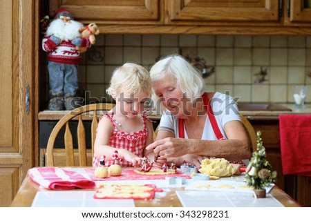 Loving caring grandmother, beautiful senior woman, baking tasty sweet cookies together with her granddaughter, cute little toddler girl, sitting at the table in classic traditional wooden kitchen. - stock photo