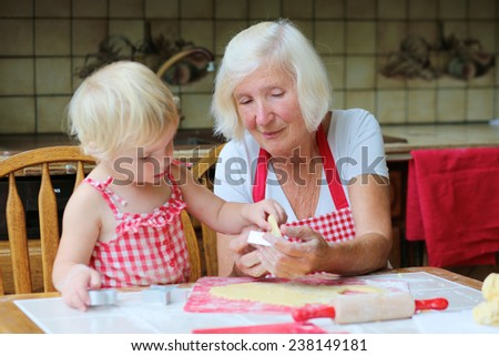 Loving caring grandmother, beautiful senior woman, baking tasty sweet gingerbread xmas cookies together with her granddaughter, cute little toddler girl, sitting in classic traditional wooden kitchen - stock photo