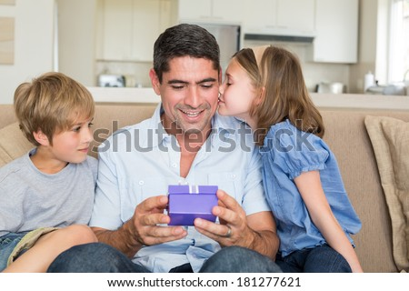 Loving children gifting father in living room - stock photo