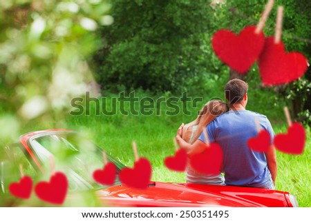 Loving couple admiring nature while leaning on their cabriolet against hearts hanging on a line - stock photo