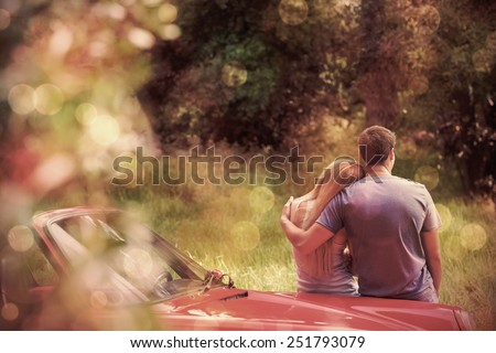 Loving couple admiring nature while leaning on their cabriolet on a sunny day - stock photo
