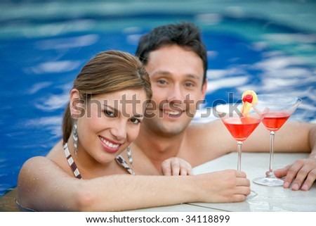 Loving couple at a swimming pool with cocktails - stock photo