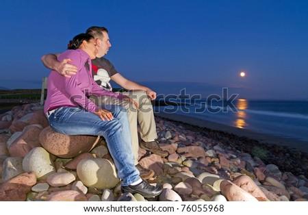 Loving Couple at full moon on irish beach - stock photo