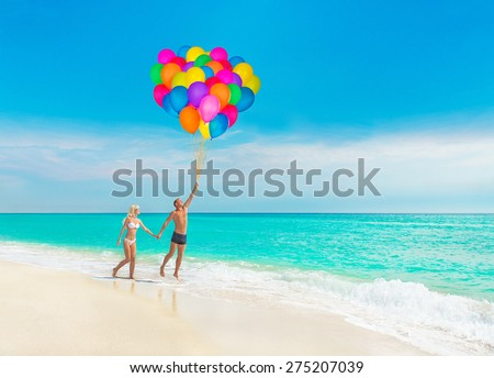 Loving couple at sea beach flying varicoloured air balloons in blue sky - stock photo