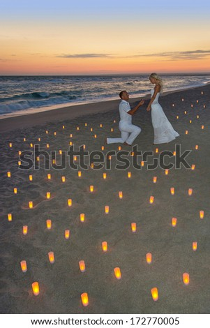 Loving couple at sea beach in candles against bright sunset - St.Valentines Day romantic concept - stock photo