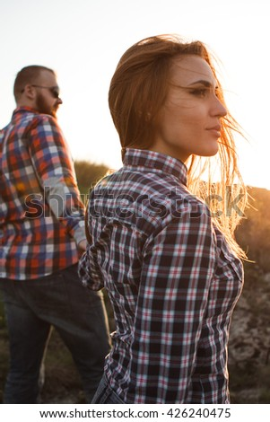 Loving couple at sunset, travel, trip. Man and woman holding hands. A man with a beard. Girl with long red hair. A couple in love on a mountain top. man and woman holding hands, girl in a shirt. - stock photo