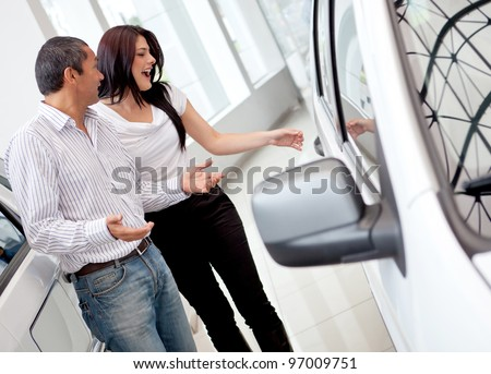 Loving couple at the dealership buying a car - stock photo