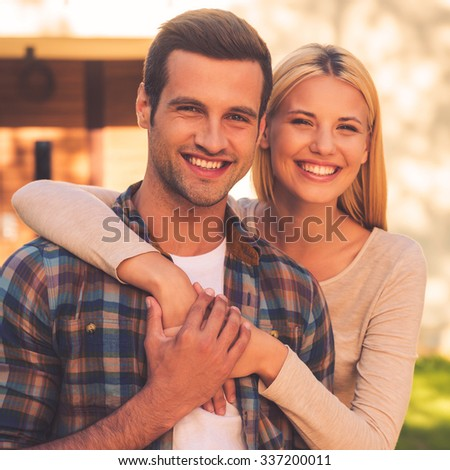 Loving couple. Beautiful young couple bonding to each other and smiling while standing against their new house - stock photo
