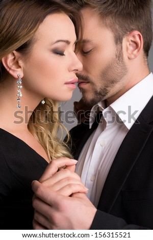 Loving couple. Beautiful young couple in formalwear standing close to each other and keeping eyes closed - stock photo