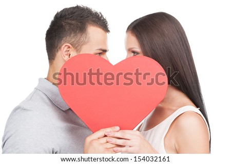 Loving couple. Beautiful young loving couple standing face to face and holding big paper heart while isolated on white