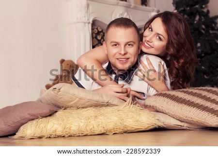 Loving couple celebrating christmas and new year at home sitting on a pillows on a floor with christmas tree on a background. Smiling and kissing and surprising each other with presents
