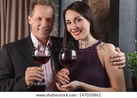 Loving couple. Cheerful middle-aged couple holding glasses with wine and smiling at camera - stock photo