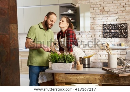 Loving couple cooking together in kitchen, woman kissing man. - stock photo