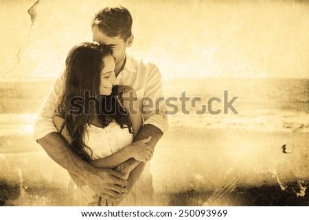 Loving couple cuddling against grey background - stock photo