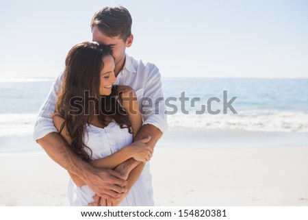 Loving couple cuddling at the beach - stock photo