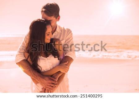 Loving couple cuddling at the beach - stock photo