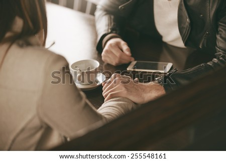 Loving couple dating at the bar, he is holding her hand and comforting her