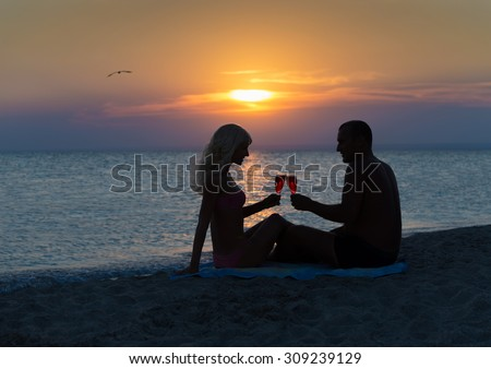 Loving couple drinking red wine at summer sandy sea beach during sunset time - stock photo