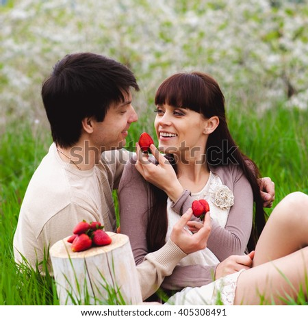 Loving couple eating strawberry outdoor - stock photo