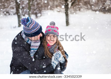 Loving couple embracing in winter park. They put colored caps and scarves. Loving warm hands to each other. Copy space. The girl hat with red hearts. - stock photo