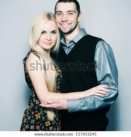 Loving couple embracing over light blue background. studio shot - stock photo