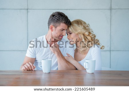 Loving couple enjoying their morning coffee together sitting at a wooden counter giving each other an affectionate nuzzle - stock photo