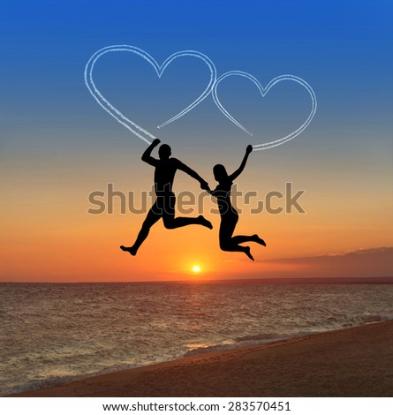 Loving couple flying at sky against sea beach and heart shaped vapour trails - happy valentines day concept - stock photo