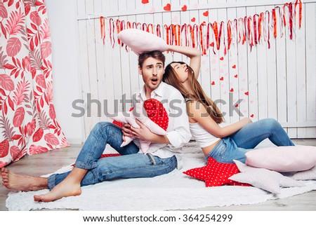 loving couple having a pillow fight - stock photo