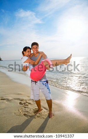 loving couple having fun carrying on the beach