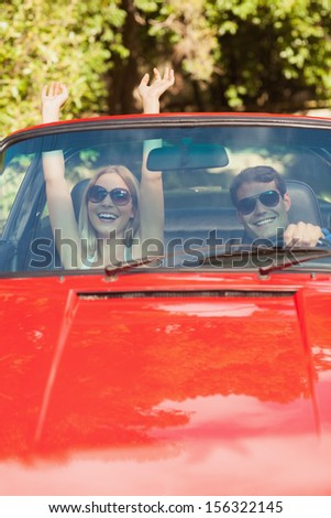 Loving couple having fun in their red cabriolet on a sunny day - stock photo