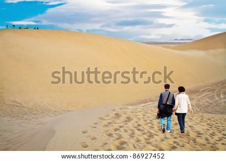 Loving couple hiking in the desert - stock photo