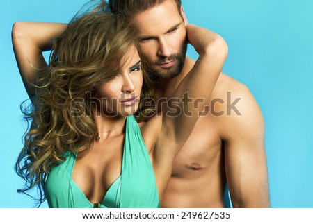 Loving couple holding each other on blue background - stock photo