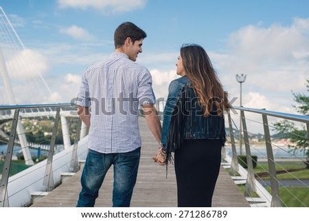 Loving couple holding hands and looking at each other - stock photo