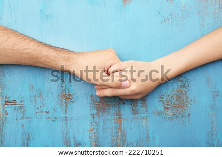 Loving couple holding hands close-up on wooden background - stock photo