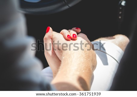 Loving couple holding hands in car - stock photo