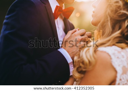 Loving couple holding hands with rings against wedding dress - stock photo