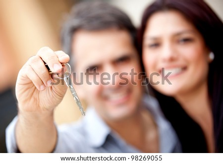 Loving couple holding keys to house or car - stock photo