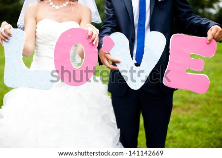 Loving couple holding letters of the word LOVE - stock photo