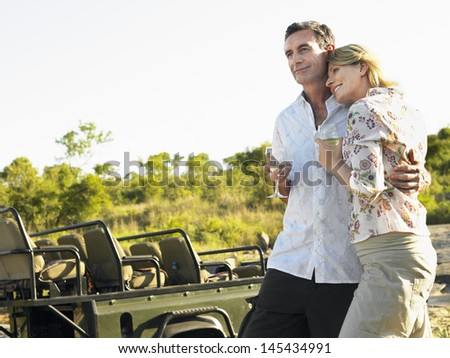 Loving couple holding wineglasses with jeep and plants in the background - stock photo