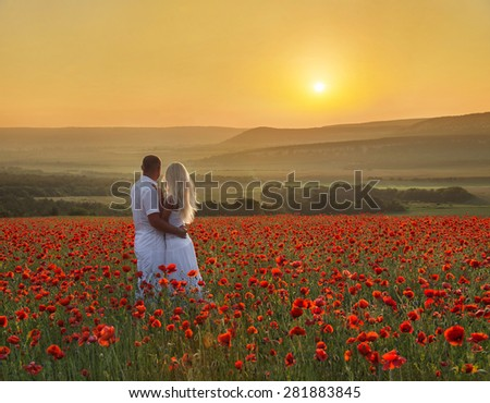 Loving couple hug one another during romantic date in poppy field with bright sunset above forest and mountains - stock photo