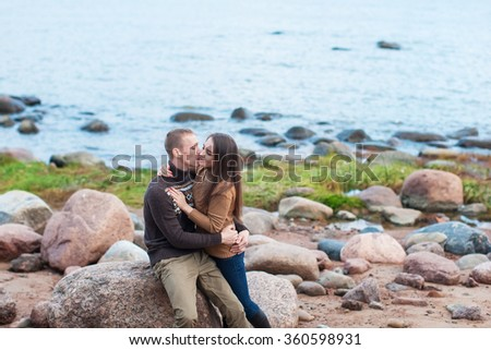 Loving couple hugging and kisses on the rocky beach
