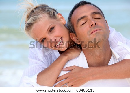 Loving couple hugging on the beach - stock photo