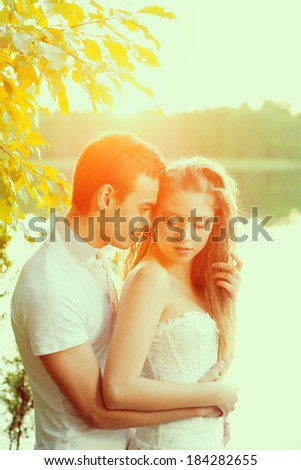 Loving couple hugging on the lake. Beautiful young woman and man in the background of the sun shining. Happy smiling Loves a date