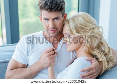 Loving couple in a close romantic embrace holding hands and cuddling as they relax together on a sofa in front of a window - stock photo