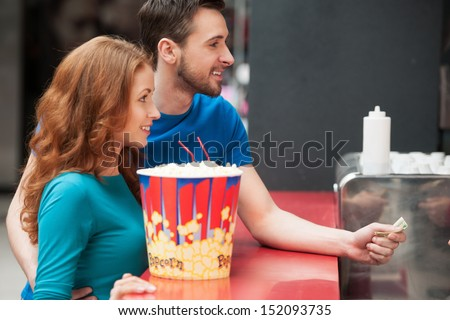 Loving couple in bar. Young loving couple buying popcorn and soda at the cinema bar - stock photo